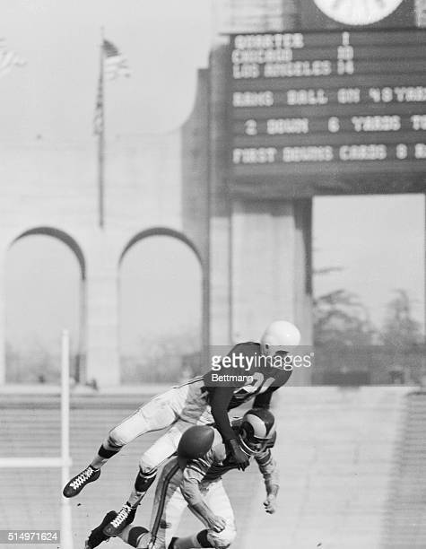 Playing leap frog for money are Cardinals' Dick Lane vaulting over the Rams' Tom Fears while breaking up a pass and Rams' Harry Thompson hurdling...