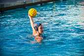 High School female water polo player holding ball high above the water looking to pass or shoot.