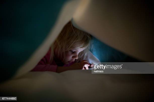 Playing on daddy's phone under the duvet