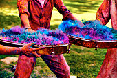Playing on Indian drums during Happy Holi holidays in India.  Frozen movement of action.  Particles of colored powder forming incredible visually effect.