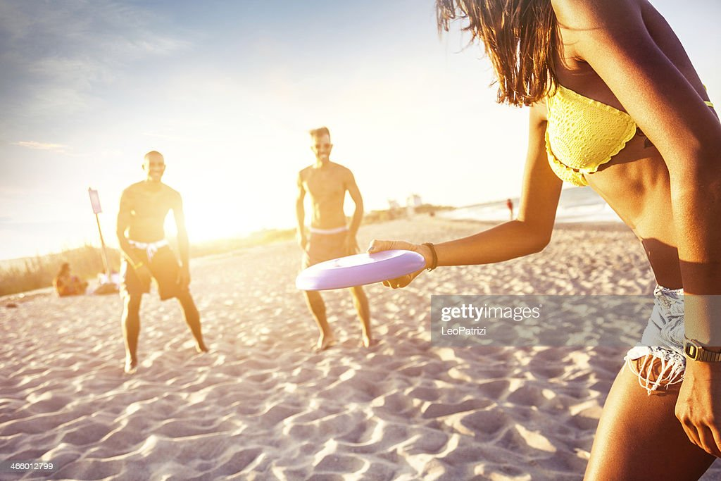 Playing on the beach with a freesbi : Stock Photo