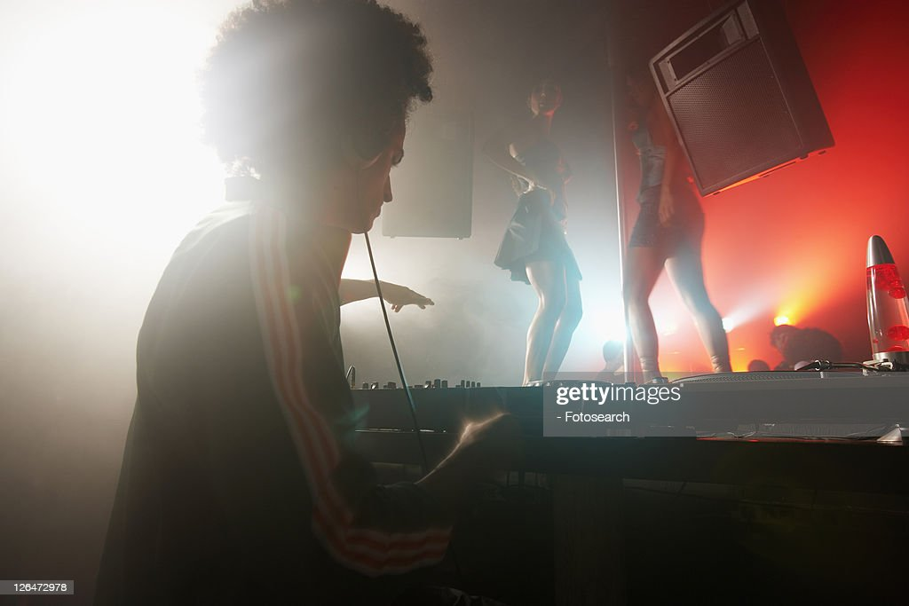 DJ playing records, dancers in background : Stock Photo