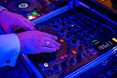 Close view on the hands of dj playing the mixer
