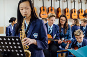 Teen student is playing the saxophone in her school music lesson. The rest of the class are in the background, out of focus.