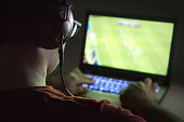 Playing video games with laptop. Young man plays online soccer or football on computer. Back view of gamer with headphones in dark or late at night. Competitive gaming, electronic sports and esports.