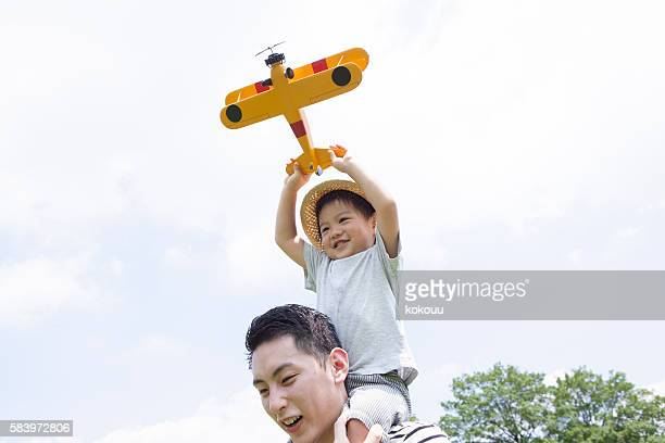 Playing with happily airplane toys in on his father's shoulder