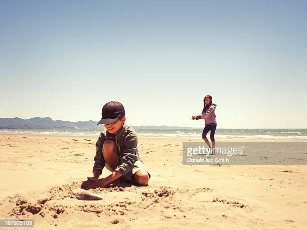 Playing with sand on beach.