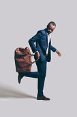 Full length of handsome young African man in full suit carrying brown leather bag on his foot while standing against grey background