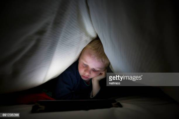 Playing with tablet under the duvet