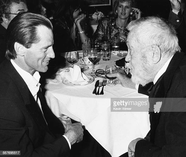 Playwright Sam Shepard talking to film director John Huston at their table at Swifty Lazar's postOscar party at Spago's Los Angeles March 25th 1986