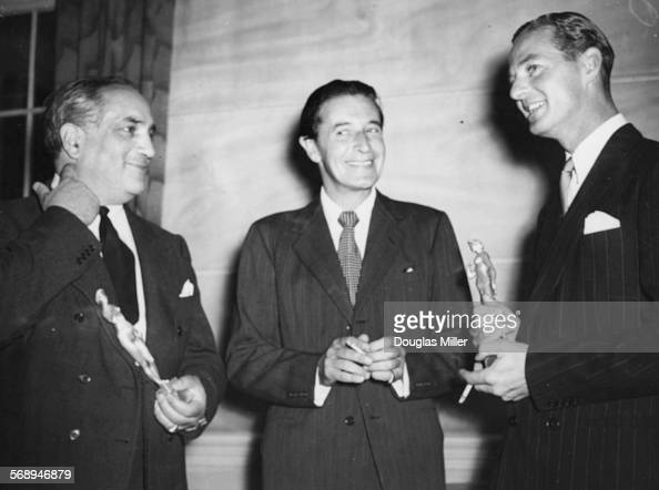 Playwright Terence Rattigan holding his award with fellow award winner Frederick Valk and Chairman of the Committee Ivor Novello at the Theatre...