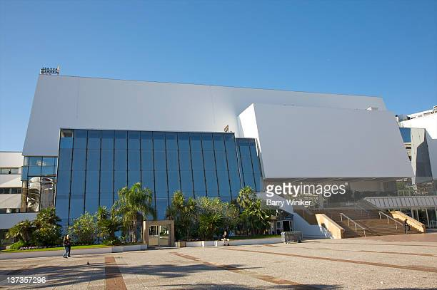 Plaza in front of white building with glass wall.