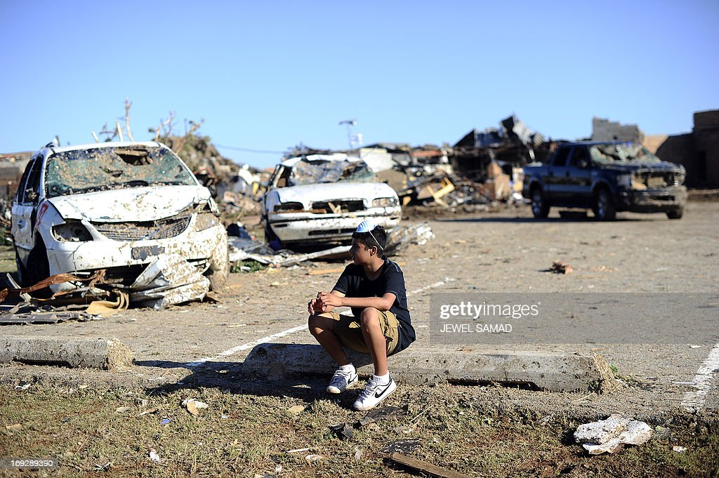 Plaza Towers Elementary School student Lavontey Rodriguez sits at the parking lot of their tornado devastated school on May 22, 2013 in Moore, Oklahoma. Seven children died in the school during the tornado. As rescue efforts in Oklahoma wound down, residents turned to the daunting task of rebuilding a US heartland community shattered by a vast tornado that killed at least 24 people. The epic twister, two miles (three kilometers) across, flattened block after block of homes as it struck mid-afternoon on May 20, hurling cars through the air, downing power lines and setting off localized fires in a 45-minute rampage. AFP PHOTO/Jewel Samad