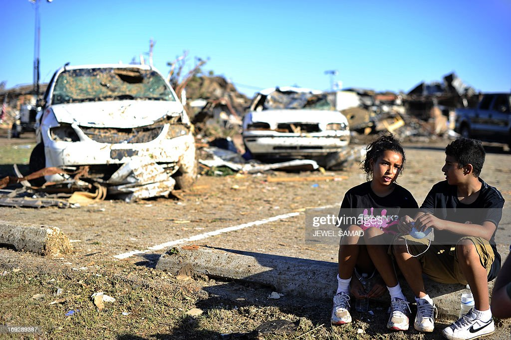 Plaza Towers Elementary School students Monica Boyd (L) and Lavontey Rodriguez sit at the parking lot of their tornado devastated school on May 22, 2013 in Moore, Oklahoma. Seven children died in the school during the tornado. As rescue efforts in Oklahoma wound down, residents turned to the daunting task of rebuilding a US heartland community shattered by a vast tornado that killed at least 24 people. The epic twister, two miles (three kilometers) across, flattened block after block of homes as it struck mid-afternoon on May 20, hurling cars through the air, downing power lines and setting off localized fires in a 45-minute rampage. AFP PHOTO/Jewel Samad