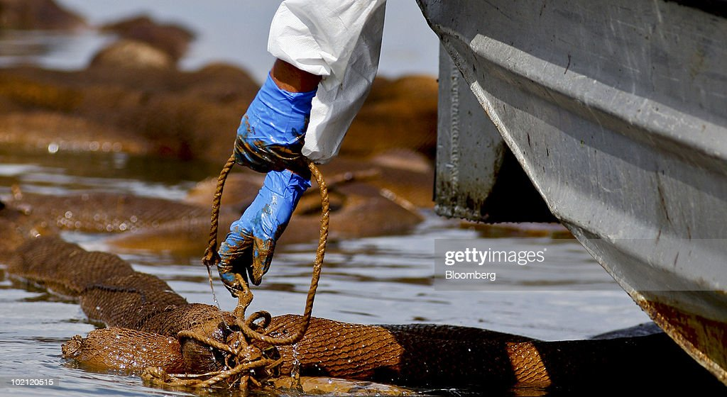 Plc contractor worker pulls up an oil-soaked absorbent boom in Bay Ronquille off the coast of Grand Isle, Louisiana, U.S., on Tuesday, June 15, 2010. The BP Plc oil spill, which began when the leased Transocean Deepwater Horizon oil rig exploded on April 20, has closed as much as 37 percent of federal waters in the Gulf of Mexico to fishing, cut offshore drilling in the U.S. by half, and polluted at least 140 miles (225 kilometers) of shoreline from Louisiana to Florida. Photographer: Derick E. Hingle/Bloomberg via Getty Images