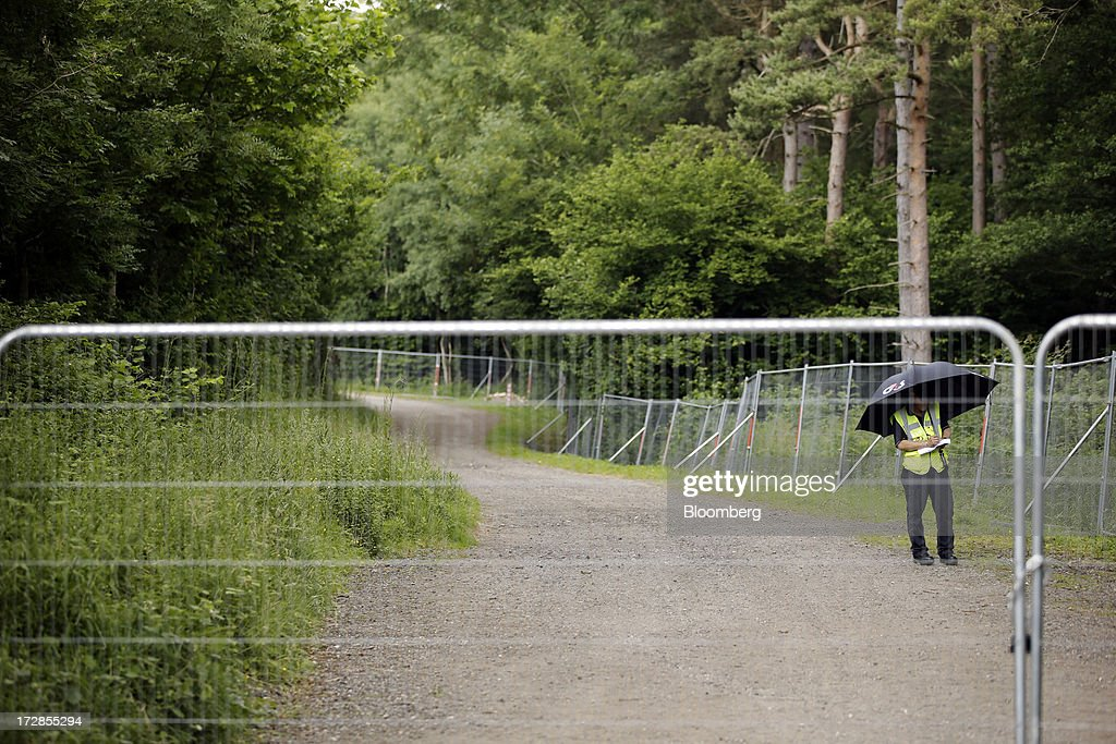Plc security guard shelters beneath an umbrella at the entrance to Cuadrilla Resources Ltd.'s exploratory shale gas drill site in Balcombe, West Sussex, U.K., on Friday, July, 5, 2013. Two areas of Surrey and Sussex hold 700 million barrels of recoverable shale oil, or more than a year's supply for Britain, the U.S. Energy Information Administration estimates. Photographer: Matthew Lloyd/Bloomberg via Getty Images