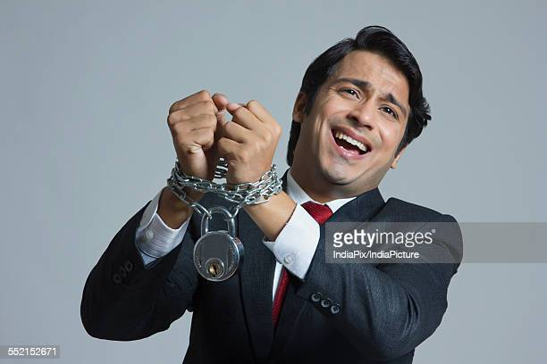 Pleading businessman tied in chain over gray background