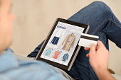 Pay it off. Pleasant man sitting on the couch and holding credit card while using tablet