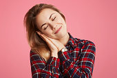 Pleased pretty young woman leans at hands, has pleasant healthy dream, rest for minute after sleepless night, celebrated birthday with friends, isolated over pink background. People, leisure concept