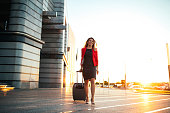 Full length portrait of a well dressed business woman pulling a suitcase at the airport.