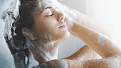 Closeup side view of attractive mid 20's woman taking a shower in her bathroom after a long exhausting day at work or college. She's gently washing her hair and skin.