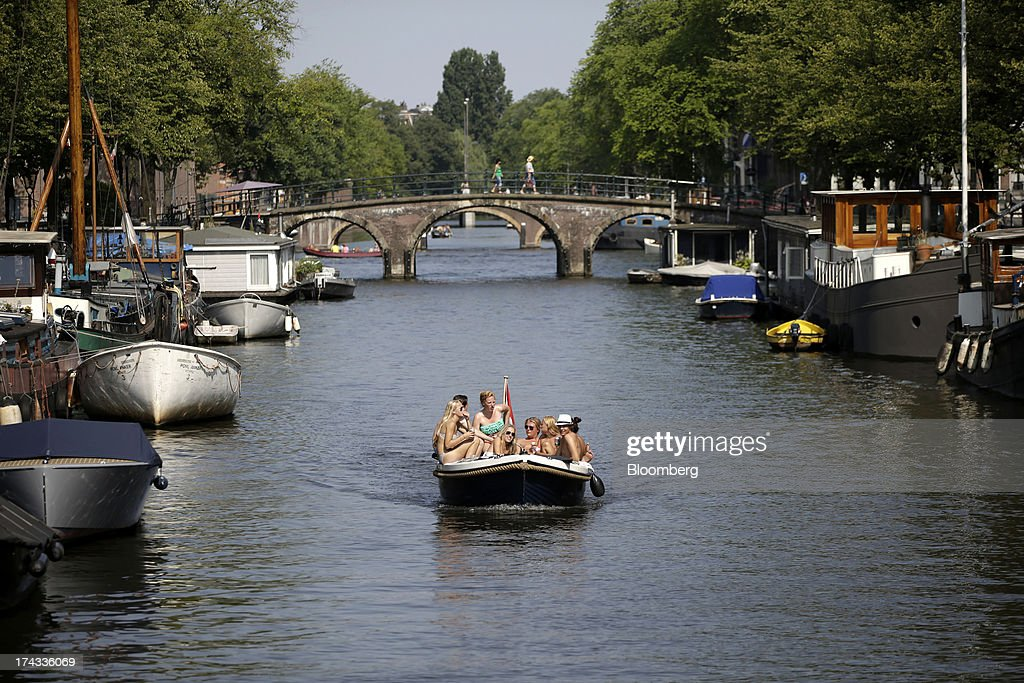 Pleasure seekers sit on a boat as it travels along the city's canal network in Amsterdam, Netherlands, on Tuesday, July 23, 2013. Dutch pension funds will be allowed to calculate liabilities on the basis of an adjusted discount rate as the government seeks to keep the retirement system viable amid low interest rates and an aging population. Photographer: Matthew Lloyd/Bloomberg via Getty Images