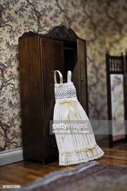 A pleated nightdress by Spanish minature designer Pillar Calle sits against a wardrobe made by David Booth who works without the use of modern...