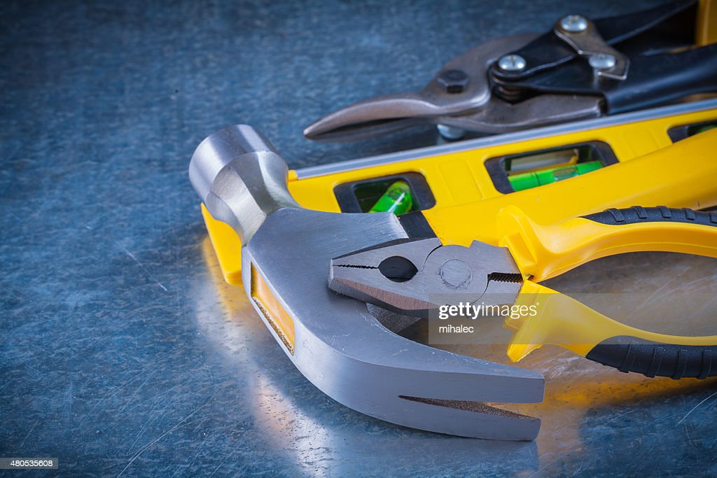 Pliers claw hammer construction level and tin snips on scratched : Stock Photo