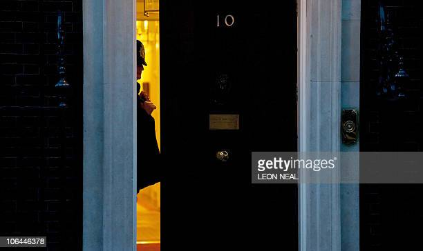A ploice officer stands inside the doorway of 10 Downing Street the official residence of British Prime Minister David Cameron in central London on...