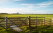 Beverley, Yorkshire, UK. Agricultural landscape of ploughed field surrounded by gated wooden fence under a bright blue sky in early spring in Beverley, Yorkshire, UK.