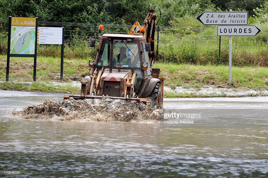 A plow clears the road to Lourdes on June 19, 2013 after the Gave de Pau river flooded the southwestern French town of Pierrefitte-Nestalas. Flash floods in southwestern France killed an elderly woman as the inundated grotto at the Roman Catholic pilgrimage site of Lourdes remained closed for a second day on June 19.