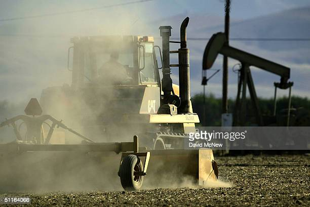 A plow kicks up dust adding to today's heavy air pollution as it passes an oil well on August 12 2004 near the town of Arvin southeast of Bakersfield...