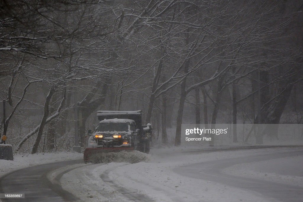 A plow truck clears a road in a snow-shrouded park on March 8, 2013 in the Brooklyn borough of New York City. As a week-old storm slowly moves out to sea, the New York City area is expecting 1 to 3 inches of snow with more in areas north and west of the city. The storm has caused flight delays at area airports and numerous schools have delayed start times.