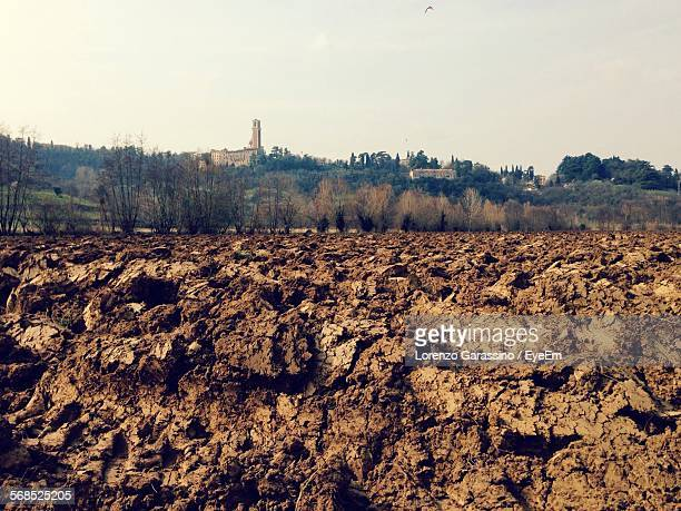 Plowed Field With Village In Background
