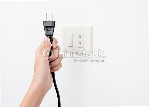 Plug On Hand Or Unplug And Outlet White Wall Background Electric Shock Stock