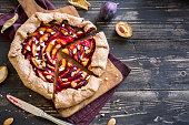 Plum Galette. Healthy homemade wholegrain fruit pie (galette) with plums, almonds and brown sugar, vegan vegetarian autumn dessert food.