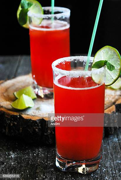 Plum margaritas in glasses on wood