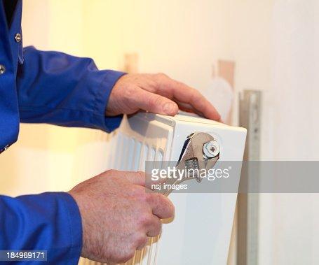 Plumber fixing a radiator.
