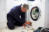 Plumber Fixing Domestic Washing Machine