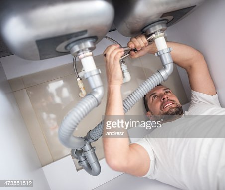 Plumber fixing pipes on the kitchen