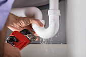 Close-up Of Male Plumber Fixing White Sink Pipe With Adjustable Wrench