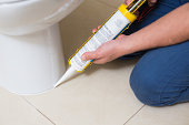 Close up of a plumber fixing toilet in a washroom with silicone cartridge
