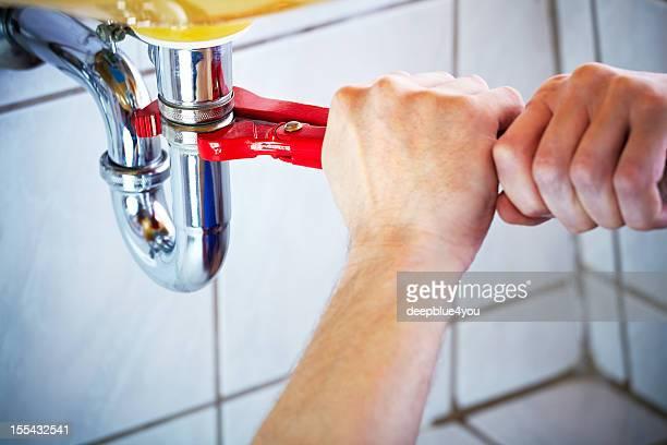 Klempner Hände holding Schraubenschlüssel und hatte ein Waschbecken im Badezimmer