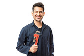 Handsome plumber holding Stillsons while smiling against white background