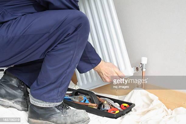 Plumber installing a radiator.