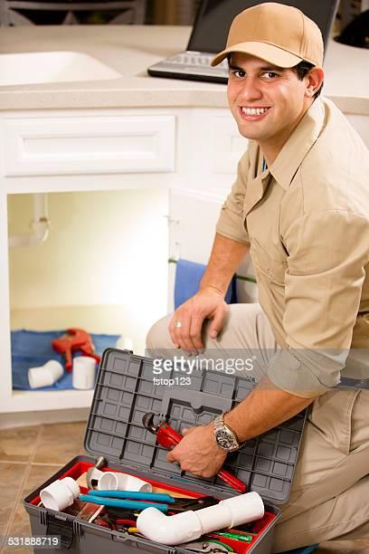 Plombier travaillant sous un évier, réparateur dans la cuisine.
