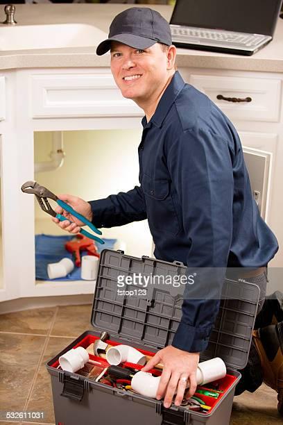 Plumber, repairman working under sink in home kitchen.