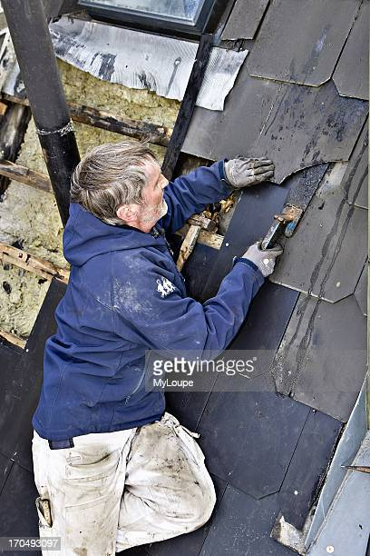 A plumber replaces old leaky roof with new slates