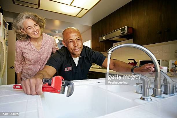Plumber testing sink for woman in kitchen