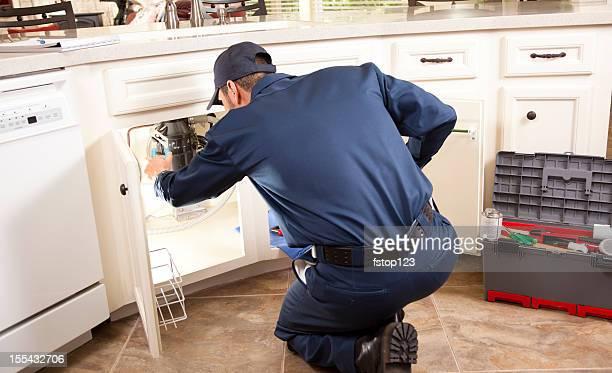 Plumber working under sink in kitchen